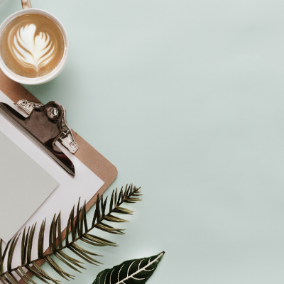 Clip board with paper with coffee and pale blue background