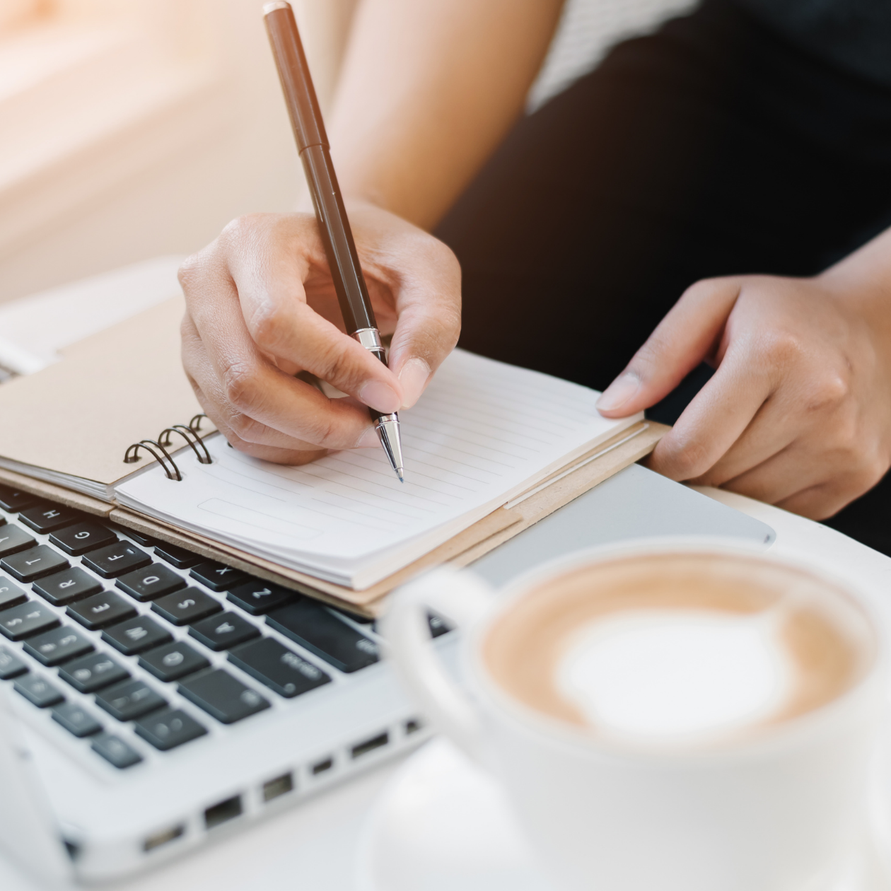 Image of lady writing in notebook, beside laptop, with coffee